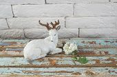 stock photo of deer family  - statuette with deer on old wood background - JPG