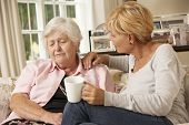 stock photo of visitation  - Adult Daughter Visiting Unhappy Senior Mother Sitting On Sofa At Home - JPG