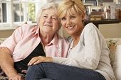 foto of senior adult  - Adult Daughter Visiting Senior Mother Sitting On Sofa At Home - JPG