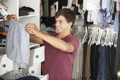 foto of wardrobe  - Teenage Boy Choosing Clothes From Wardrobe In Bedroom - JPG
