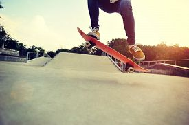 image of skateboard  - closeup of skateboarder legs skateboarding at skatepark - JPG