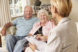 image of retirement  - Retired Senior Couple Sitting On Sofa Talking To Financial Advisor - JPG