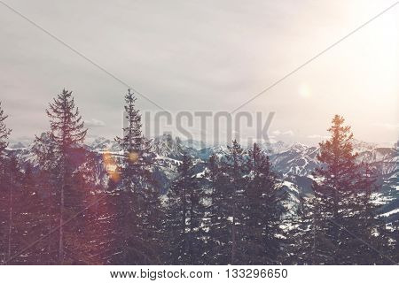 Bright flare from sun in winter storm clouds over mountain range with snow and forest of evergreens