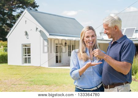 Cheerful senior couple standing outside their new house with keys. Retired man giving new house keys