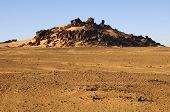 foto of denude  - Denuded and eroded landscape with granite hill in the Sahara desert Libya - JPG