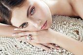 Beleza com anel de diamante no fundo de pérolas