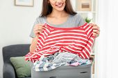 Woman holding freshly washed shirt indoors. Laundry day poster