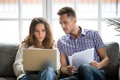 Focused Worried Couple Paying Bills Online On Laptop With Documents Sitting Together On Sofa At Home poster