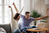 Excited Man And Woman Screaming With Joy Raising Hands Looking At Laptop Screen Sitting On Sofa At H poster