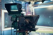 Television studio with camera and lights - recording TV NEWS. Shallow depth of field - focus on came poster