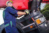 Semi Truck Maintenance By Professional Truck Mechanic. Caucasian Technician Preparing Truck Cabin Fo poster