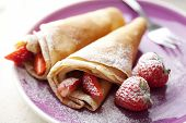 stock photo of crepes  - french style crepes with fresh strawberries and caster sugar - JPG
