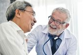 Happiness People.  Senior Male Doctor And Asian Male Patient Are Talking In The Medical Room Togethe poster