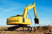 Heavy excavator loader at soil moving works in summer sandpit