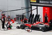 SEPANG, MALAYSIA - APRIL 8: Marussia Virgin Racing team crew checks on Timo Glock's car on the first
