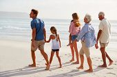 Multi Generation Family On Vacation Walking Along Beach Together poster