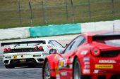 SEPANG, MALAYSIA - JUNE 19: LMP Motorsport's white Ferrari takes turn 4 ahead of the Jimgainer's red