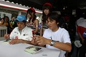 SEPANG - JUNE 19: Atsushi Yogo and Manabu Orido (cap) of JLOC sign autographs for fans at the Sepang