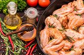 Close Up Raw Chickens Wings Covered In Honey And Spices In Frying Pan, Oil, Honey, Vegetables And Sp poster