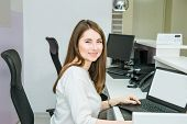 Portrait Of Smiling Skilled Administrative Manager Working On Laptop With White Empty Screen In Offi poster