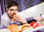 Young male having breakfast in bed, biting croissant