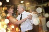Romantic senior couple dancing together at dance hall poster