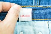 Постер, плакат: Clothing Label With Laundry Instructions Close up Of Person Reading The Clothing Label Showing Wash