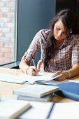 Retrato de una bella estudiante escribir un ensayo