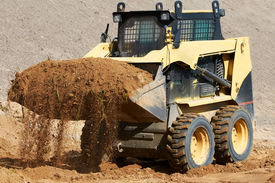 foto of skid-steer  - skid steer loader moving sand soil at construction area outdoors - JPG