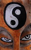 picture of totem pole  - Yin Yang symbol carved into a totem pole with eyes underneath - JPG