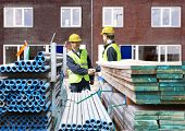 Two building contractors shaking hands behind stacks of scaffolding material, in front of a newly co
