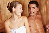 Attractive young couple in sauna looking at each other and smiling