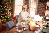 Adorable senior woman smiling happy and confident. Sitting prepared to celebrate christmas at home poster