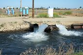 image of gushing  - Water gushes from pipe into irrigation canal on a California farm - JPG