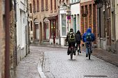 A trio of students cycling through a European town on a damp winter day