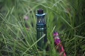 The Electronic Cigarette Lies In The Green Grass. Steam Generator In The Grass. Electronic Cigarette poster