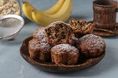 Banana Muffins With Oatmeal Flakes Sprinkled With Icing Sugar On A Coconut Plate, Horizontal Orienta poster