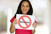 Teen girl holding a card that says no bullying poster