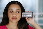 Teen girl listening to a tin can phone