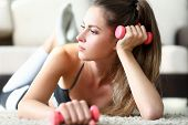 Close-up Of Wonderful Woman With Collected Hair Wearing Sportswear. Beautiful Girl Lying On Carpet A poster