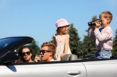 Happy father, mother and two children ride in convertible car and play; focus on man