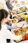Business people around buffet table catering food at company event