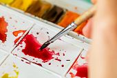 Watercolor Palette. An Artist Mixes Colors On A Palette. Red Paint On A White Palette. Plastic Box W poster