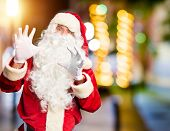Middle age handsome man wearing Santa Claus costume and beard standing afraid and terrified with fea poster