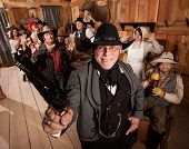 pic of antique wheelchair  - Smiling armed sheriff and group of people with hands up in saloon - JPG