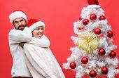 Happy Family In Santa Hats Having Fun Near Christmas Tree. Happy Couple Fooling Around While Prepari poster