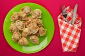 Dumplings On A Green Plate Against A Red Background. Dumplings Meat In Tomato Sauce Top View. Asian  poster