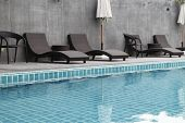 Swimming Pool With Pool Chair Set And Umbrella. The Pool Is Ready For This Summer. poster