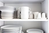 White Cupboard With White Crockery In The Kitchen, Various Clean Dishes poster