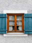Window On A Gray Wall With Blue Shutters. Wooden Brown Window Frame With White Curtains. Window With poster